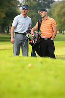 Young men standing on golf course carrying bags