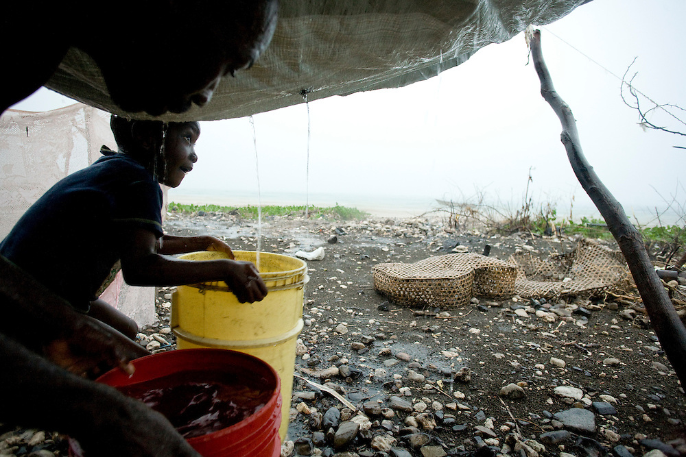Sourin Nicholene, age 5, and his father Pradall Nicholene drain water from a holes in the tarp roof into buckets for drinking water. The family stands under a tarp shelter during the rain in their flooding camp. The Nicholene family was displaced by the January earthquake.