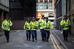 "© Licensed to London News Pictures . 22/08/2015 . Manchester , UK . Police run through along a back street to break up a fight between anti-fascists and far-right protesters . Far-right nationalist group , "" North West Infidels "" and Islamophobic , anti-Semitic and white supremacist supporters , hold a rally in Manchester City Centre . Photo credit : Joel Goodman/LNP"