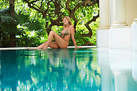 Young woman sitting by swimming pool portrait