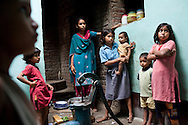 """Sitara's (aged 35, unseen) 7 children (5 daughters & 2 sons) cook for the breaking of fast during the month of Ramadhan and take care of each other in their small house in a village in Allahabad, Uttar Pradesh, India. """"I wish that I could stop getting pregnant but our religion says that children are a gift of God."""" says Sitara, an illiterate muslim lady whose husband works as a vegetable vendor in the local village market. They have resisted all advises of permanent sterilization from the local village-level health workers. Children from left to right : Ajman (5), Rani (7), Chandni (14), Roshni (10), Tamanna (8 months), Asif (3), and Sufia (8). Photo by Suzanne Lee / Panos London"""