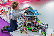 A young boy enjoys playing with the Mighty Mountain Mine, by Marbel, winner of best in show Wooden Toys - The London Toy Fair opens at Olympia exhibition centre. Organised by the British Toy and Hobby Association it is the only dedicated toy, game and hobby trade exhibition in the UK. It runs for three days, with more than 240 exhibiting companies ranging from the large internationals to the new start up companies.