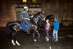 © Licensed to London News Pictures. 05/11/2015. London, UK. Demonstrators come face to face with mounted police during An anti-capitalist  protest organised by the group Anonymous outside Parliament in Westminster on bonfire night 05, November 2015. Bonfire night, also known as Guy Fawkes night, is an annual commemoration of when Guy Fawkes, a member of the Gunpowder Plot, was arrested for attempting to blow up the House of Lords at parliament.   Photo credit: Ben Cawthra/LNP