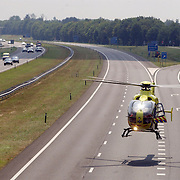NLD/Blaricum/20050711 - Gekantelde vrachtwagen met gewonde chauffeur snelweg A27 ter hoogte Blaricum, traumaheli land op de snelweg..helicopter