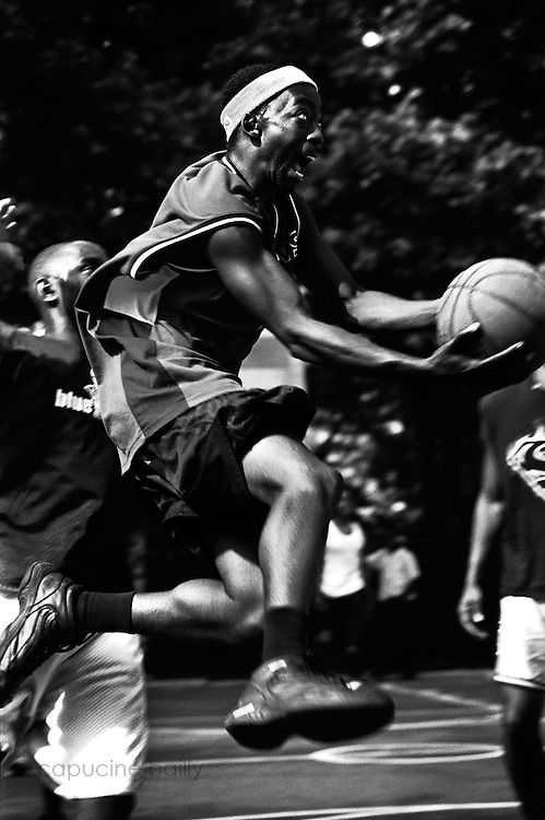 "June 3rd 2004. New York, New York. United States..Located in the heart of Greenwich Village, the West 4th Street basketball Court, known as ""The Cage"", offers no seating but attracts the best players and a lot of spectators as soon as spring is around the corner..Half the size of a regular basketball court, it creates a fast, high level of play. The more people watch, the more intense the games get. « The Cage » is a free show. Amazing actions, insults and fights sometimes, create tensions among and inside the teams. The strongest impose their rules. Charisma is present..""The Cage"" is a microcosm. It's a meeting point for the African American street culture of New York. Often originally from Jamaica or other islands of the Caribbean, they hang out, talk, joke, laugh, comment the game, smoke… Whether they play or not, they're here, inside ""The Cage"". Everybody knows everybody, they all greet each other, they shake hands and hug: ""Yo, whasup man?"""