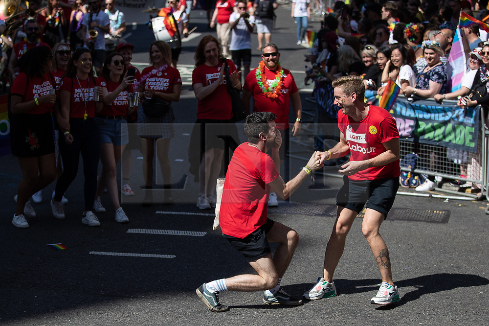 © Licensed to London News Pictures . 24/08/2019. Manchester, UK. What appears to be a marriage proposal between two men in the LGBT+ Labour float . The 2019 Manchester Gay Pride parade through the city centre , with a Space and Science Fiction theme . Manchester's Gay Pride festival , which is the largest of its type in Europe , celebrates LGBTQ+ life . Photo credit: Joel Goodman/LNP
