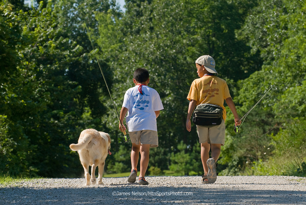 Nine- and seven-year-old brothers with a yellow Labrador retriever walk along a road to go fly fishing on the James River, Missouri.