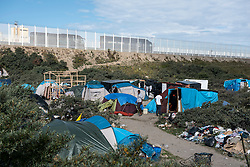 © London News Pictures. Calais, France. Lorries pass by an immigrant camp known as 'The Jungle' on the outskirts of Calais. Migrants attempting to reach the UK via the Eurotunnel at Calais in France. The situation has reached crisis point, which French police over run by attempts to cross the border. Photo credit: Ben Cawthra /LNP