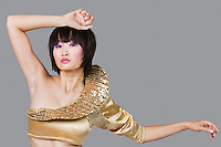 Portrait of young woman in golden costume over gray background