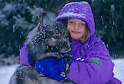 Young gilr with family pet, a Keeshond dog<br /> Winnipeg<br /> Manitoba<br /> Canada
