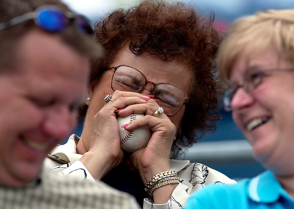 """Syracuse, NY / 2004 - Helen Brown of Liverpool laughs and squeezes the foul ball she just caught at the Syracuse Skychiefs (Toronto Blue Jays AAA affiliate) baseball game. """"It just fell into my lap,"""" she said. Photo by Mike Roy / For The Syracuse Post-Standard"""