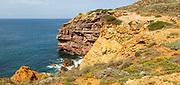 Coastal orange coloured crumbling  cliffs rise from Atlantic Ocean at Cabo de São Vicente, Cape St Vincent, Algarve, Portugal, southern Europe