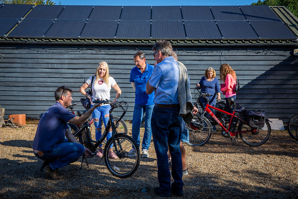 A tour guide demonstrates an electric bike to a group of people who will be taking the bikes on a tour outside the UK Electric Bike Centre, Staplehurst, Kent, England, UK.  (photo by Andrew Aitchison / In pictures via Getty Images)