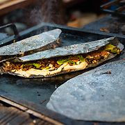 Blue corn quesadilla grilling on a hot plate