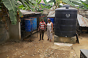Aniema Edem checking on her generator. <br /> <br /> Aniema runs 'Rasa Venture', a frozen food and ice business.<br /> <br /> With frequent power cuts the generator and a good supply of fuel is essential to maintain her frozen stock.<br /> <br /> Aniema was a contractor living in Lagos, working for ExxonMobile. She used to travel home to this area to visit her aging parents and she noticed that the convenient frozen food, widely available in Lagos, were not available in Uyo. She saw a gap in the market and decided to establish her business. <br /> <br /> She is a member of a women's business group and through them heard about Youth for Technology's training and the business support text messaging service.<br /> <br /> The main things she learnt from the training was around risk management and from the text messaging it was around staff management.