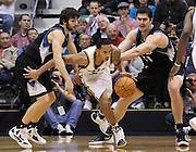 Utah Jazz guard Devin Harris, center, squeezes through the defense of Minnesota Timberwolves guard Ricky Rubio of Spain, left and center Darko Milicic of Serbia, right, during the first half of an NBA basketball game, Saturday, Jan. 21, 2012, in Salt Lake City. (AP Photo/Colin E Braley)