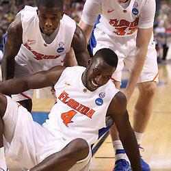 Mar 17, 2011; Tampa, FL, USA; Florida Gators forward/center Patric Young (4) is helped up by teammates guard Kenny Boynton (1) and forward Erik Murphy (33) during first half of the second round of the 2011 NCAA men's basketball tournament against the UC Santa Barbara Gauchos at the St. Pete Times Forum.  Mandatory Credit: Derick E. Hingle
