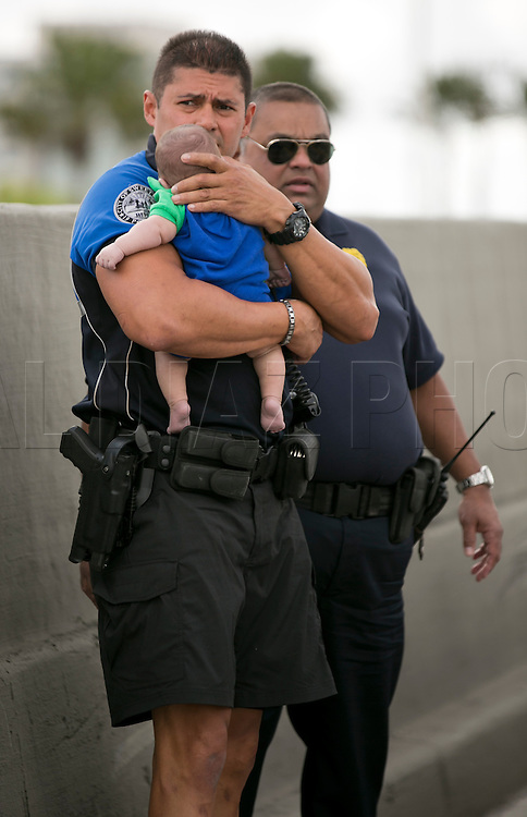 Sweetwater officer Amauris Bastidas keeps a watchful eye waiting for paramedics after aiding a five-month-old Sebastian de la Cruz who stopped breathing. The baby's aunt performed CPR after pulling her SUV over on the side of the road along the west bound lane on Florida state road 836 just east of 57th Avenue around 2:30pm on Thursday, February 20, 2014.