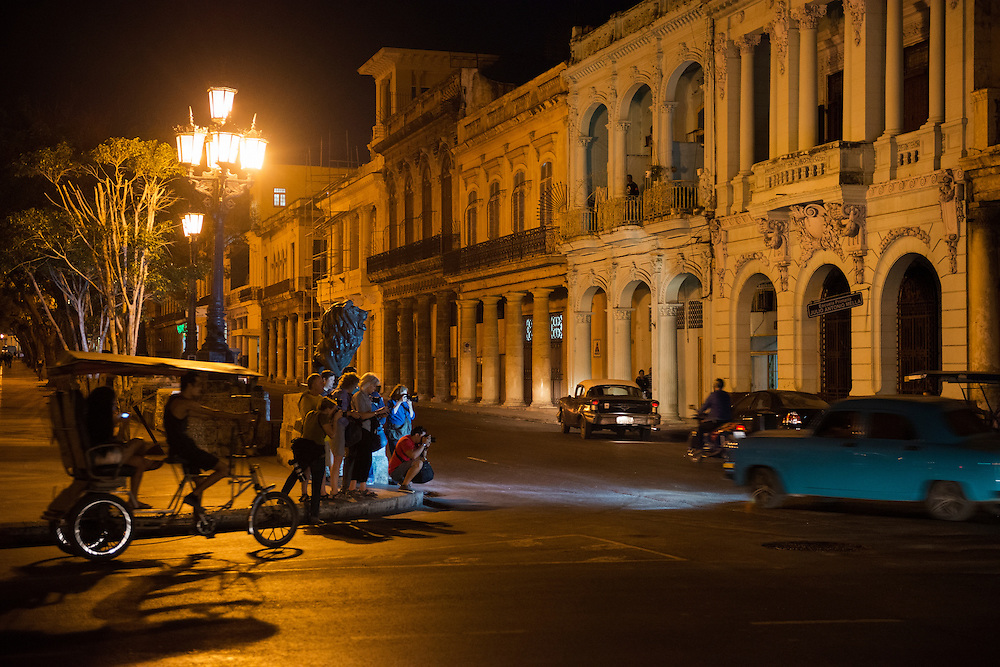 A group of photographers visiting the Cuban capital Havana stand on a street corner at night, attempting panning shots of vintage cars driving past. The street is Paseo del Prado.