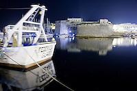 Vista del castello angioino che si riflette nell'acqua del porto di notte, Gallipoli (LE)