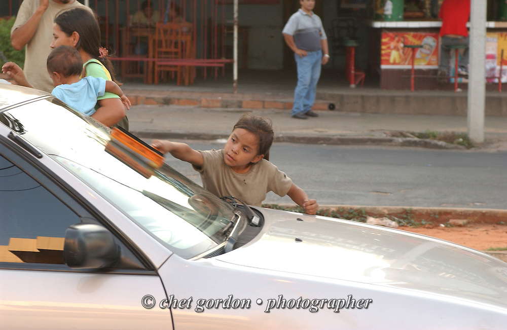 ASUNCION, PARAGUAY.  Young Paraguayan street girl cleans a windshield in Asuncion, Paraguay on Thursday evening, March 16, 2006. Hundreds of street children, some as young as 4 years old and their parents, work the diesel fumed streets of the capital city by squeegeeing windshields, panhandling and selling various items to drivers.