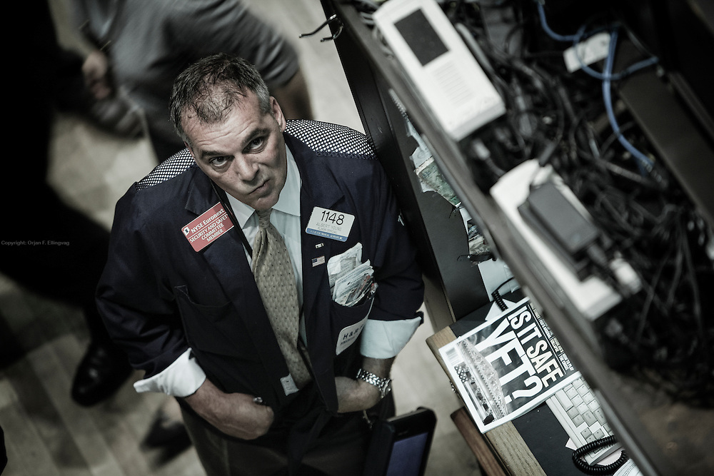 """VOLATILE MARKET: In September 2008, a floor trader at the NYSE - New York Stock Exchange - looks up on the ticker while a Business Week issue next to him asks """" Is it safe yet?"""""""