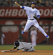 Kansas City Royals shortstop Alcides Escobar (2) turns a double play with a leaping throw over Tampa Bay Rays  base runner Sean Rodriguez (1) during the seventh inning at Kauffman Stadium.