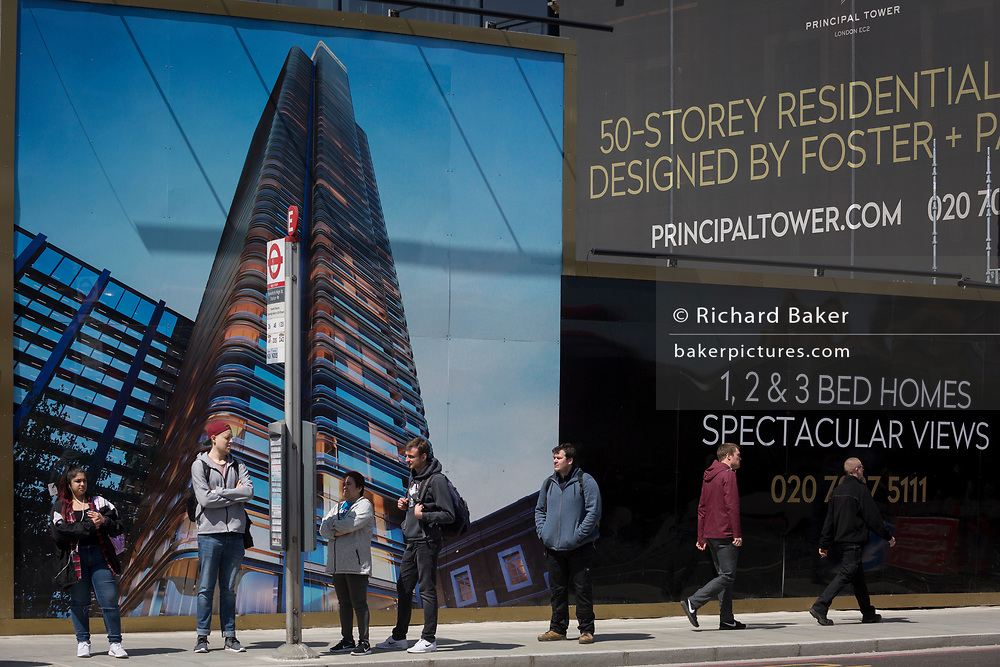 travellers wait for a bus under a construction hoarding showing the Foster-designed Principal Tower that's under construction on Shoreditch High Street, on 10th May 2017, in London, England.