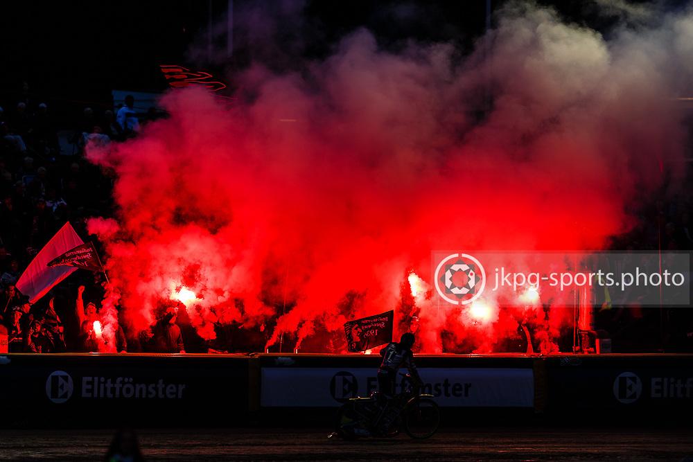 150916 Speedway, SM-final, Vetlanda - Indianerna<br /> En av f&ouml;rarna i Indianerna k&ouml;r med flagga fram&ouml;r de egna fansen / supportrarna f&ouml;r matchen. Som anv&auml;nder pyro-teknik / bengaliska eldar.<br /> Speedway, Swedish championship final,<br /> One of the drivers with a flag in front of the fans of Indianerna. The fans are using fireworks / bengal fire.<br /> &copy; Daniel Malmberg/Jkpg sports photo