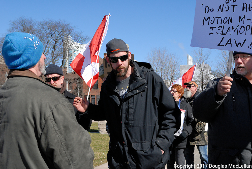 CANADA, Windsor. 04 March 2017. A Canadian Coalition of Concerned Citizens demonstration at City Hall at noon is met by a counter demonstration group. There is some minor pushing, heated debate and occasional threats. The demonstration is spurred in part by M-103, a federal anti-Islamophobia motion.