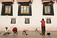Tibetan Buddhist pilgrims prostrate themselves before the Jokang, Tibet's most holy monastery, in Lhasa, Tibet.