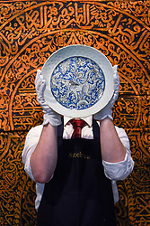 "© Licensed to London News Pictures. 18/10/2019. LONDON, UK. A technician presents a ""Safavid blue and white pottery dish depicting a lion"", Persia, 17th century (Est. GBP8,000-12,000).  Preview of Islamic, Indian and Middle Eastern art to be auctioned at Sotheby's, New Bond Street, on 22 and 23 October.  Photo credit: Stephen Chung/LNP"