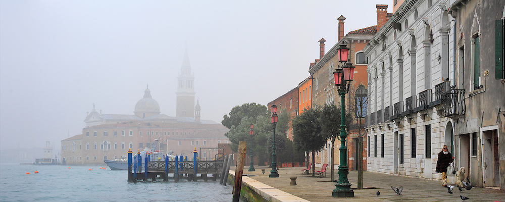 A lady from Venice walking her dog on a cold and foggy morning of mid January. Taken at the Fondamenta of Giudecca looking north, with San Giorgio Maggiore in the background. Stitched from eight vertical frames.