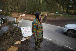 © Licensed to London News Pictures. 02/03/2017. Coldharbour, UK. A protestor waves at a supportive driver passing the 'Protection Camp' on Leith Hill. Activists have constructed and occupied a fort and some trees on the site of a proposed oil well. Planning permission for 18 weeks of exploratory drilling was granted to Europa Oil and Gas in August 2015 after a four-year planning battle. The camp was set up by protestors in October 2016 in order to draw  attention to plans to drill in this Area of Outstanding Natural Beauty (AONB) in the Surrey Hills. The camp has received support from the local community.  Photo credit: Peter Macdiarmid/LNP