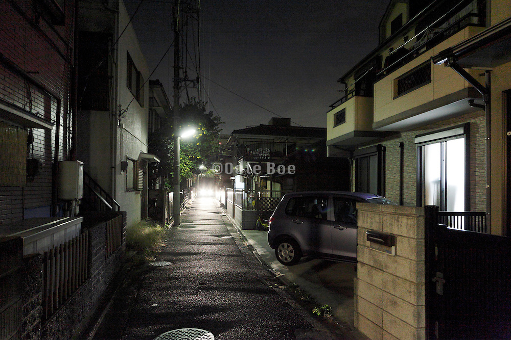 car driving through a residential neighborhood at night Japan