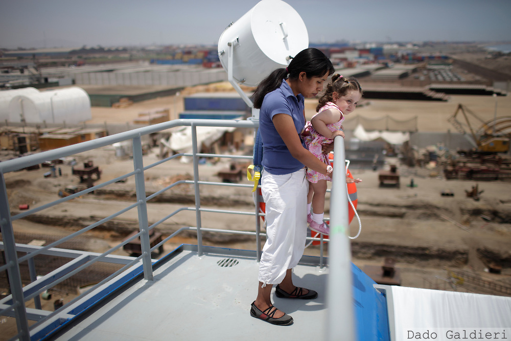 Baby sitters take care of children during the inauguration of a Peruvian built cargo ship in Callao, Lima, Peru, Thursday, March 10, 2011.