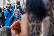 UNITED KINGDOM, London: 16 February 2018 Shocked passers by take pictures of a group of female PETA (People for the Ethical Treatment of Animals) protesters outside of 180 The Strand, the venue for London Fashion Week. The activists had 'Wear Your Own Skin' painted on their bodies to encourage passers by not to wear animal derived materials. Rick Findler / Story Picture Agency