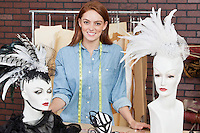 Portrait of female fashion designer standing by table with fascinators on mannequin