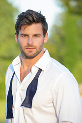 hot man at sunset in a loose bow tie and shirt