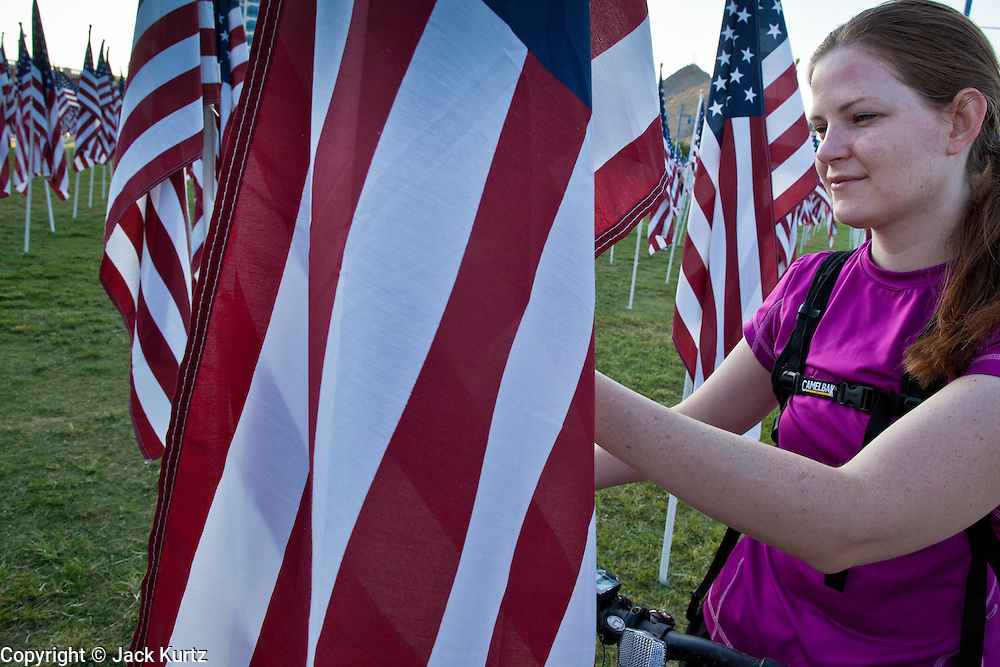 """10 SEPTEMBER 2011 - TEMPE, AZ:   JULIANNE ANDERSON, from Tempe, AZ, looks at a flag in the """"Healing Field"""" in Tempe, Saturday. The """"Healing Field,"""" a display of 2,996 flags, one for each person killed in the September 11 terrorists attacks on the World Trade Center in New York City and Washington DC, have become an annual tradition in Tempe, AZ. The event is sponsored by the National Exchange Club.       PHOTO BY JACK KURTZ"""