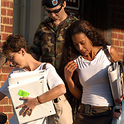 FORT BRAGG, NC- AUGUST 6: Pfc. Lynndie England (Center) leaves from a Friday's hearing with her mother Terrie England (L)  and defense investigator Kathleen Johnson (R) at the Staff Judge Advocate Building on Fort Bragg in Fayetteville, NC on 8/6/04 for her Article 32 investigation hearing. England is charged with several counts, including one specification of conspiring to commit maltreatment of an Iraqi detainee, three specifications of assault against Iraqis, and several others. (Photo by Logan Mock-Bunting)