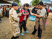 26 OCTOBER 2016 - NUPO TEMPORARY SHELTER, MAE CHAN, TAK, THAILAND: A Thai defense volunteer helps a disabled Burmese refugee woman get to a truck that will take her back to Myanmar. Sixtyfive Burmese refugees living in the Nupo Temporary Shelter refugee camp in Tak Province of Thailand were voluntarily repatriated to Myanmar. About 11,000 people live in the camp. The repatriation was the first large scale repatriation of Myanmar refugees living in Thailand. Government officials on both sides of the Thai / Myanmar border said the repatriation was made possible by recent democratic reforms in Myanmar. There are approximately 150,000 Burmese refugees living in camps along the Thai / Myanmar border. The Thai government has expressed interest several times in the last two years in starting the process of repatriating the refugees.     PHOTO BY JACK KURTZ