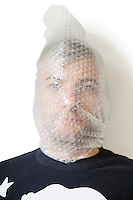 Portrait of man wrapped in bubble wrap