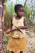 Rwanda, Virunga Mountains, young girl of five with a piece of sugarcane