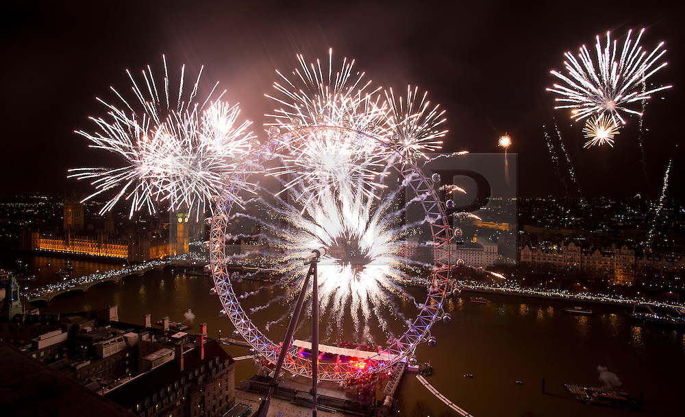 © London News Pictures. 01/01/2013. London, UK. A spectacular fireworks display lights up the London skyline just after midnight on January 1, 2013 in central London as part of the capitals New Year's Eve celebrations. Thousands of people lined the banks of the River Thames in London to see in the New Year. Photo credit: Ben Cawthra/LNP.