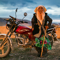 Gamila, 83, of Sagog, Mongolia, poses against her family's Russian motorcycle at sunset. Gamila had never had a color photo taken of her before, and died just days after this photo was taken.