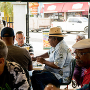 MIAMI, FLORIDA, APRIL 22, 2017<br /> Men and women play dominoes while others watch in Miami's Little Havana neighborhood's Maximo Gomez Domino Park. Many Miami Cubans voted for Donald Trump in the general elections. Trump will soon complete his first 100 days as United States President.<br /> (Photo by Angel Valentin/Freelance)