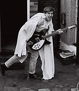 Teenager wrapped in a white sheet and holding a guitar, London, UK, 1983