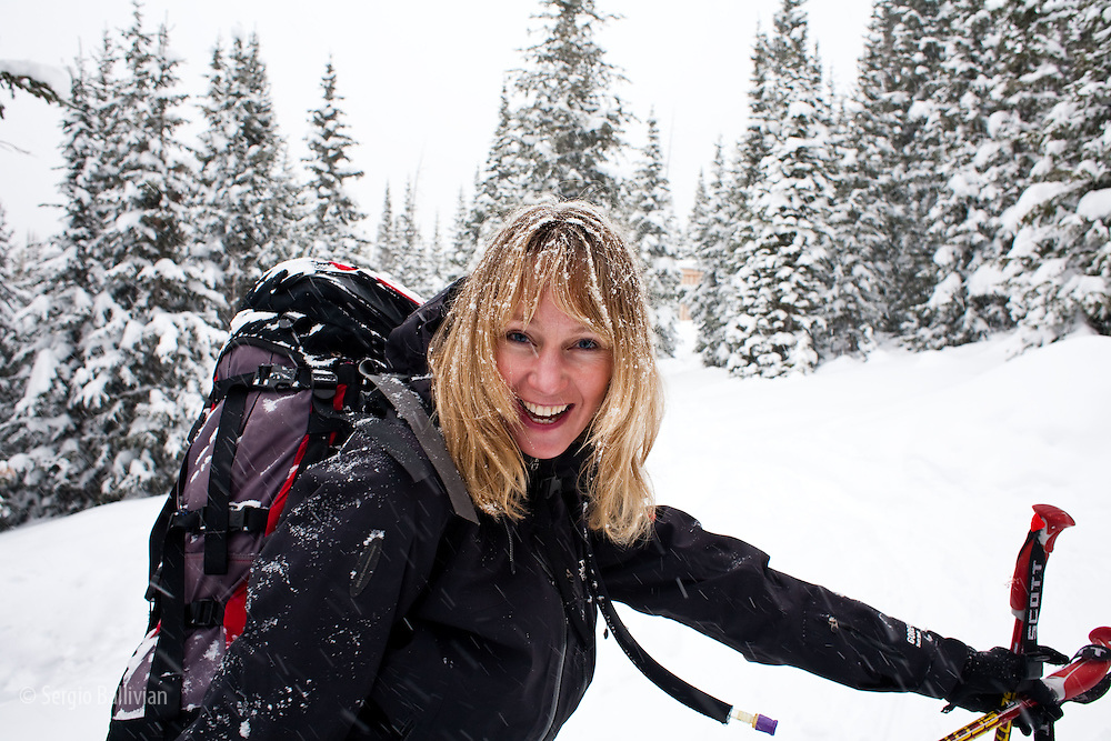 A woman smiles toward the camera while on a ski tour to a hut in Colorado in winter.