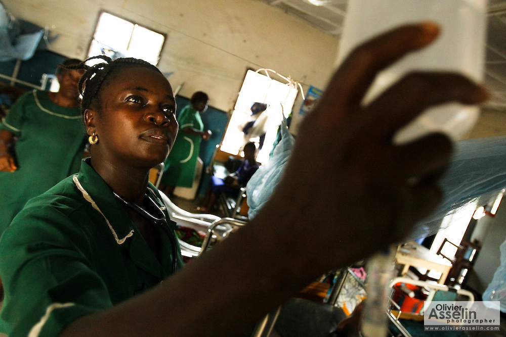 A MCH aide checks the drip of a patient in the maternity ward of the Magburaka government hospital in the town of Magburaka, Sierra Leone on Monday March 15, 2010.
